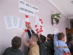 Діти розміщують сердечки з порадами та побажаннями  на силуетах людей, постраждалих від торгівлі людьми.
